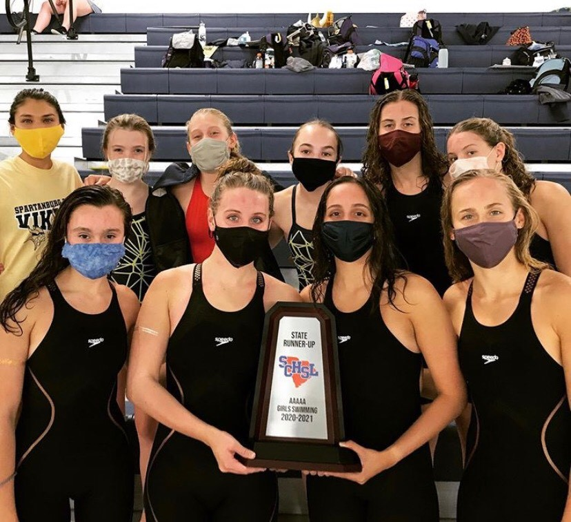 The varsity girls swim team poses with their trophy after placing second in the 5A state championship.