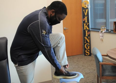 Lacing up his sneakers, Principal Vance Jones shows off a little piece of his expansive shoe collection.
