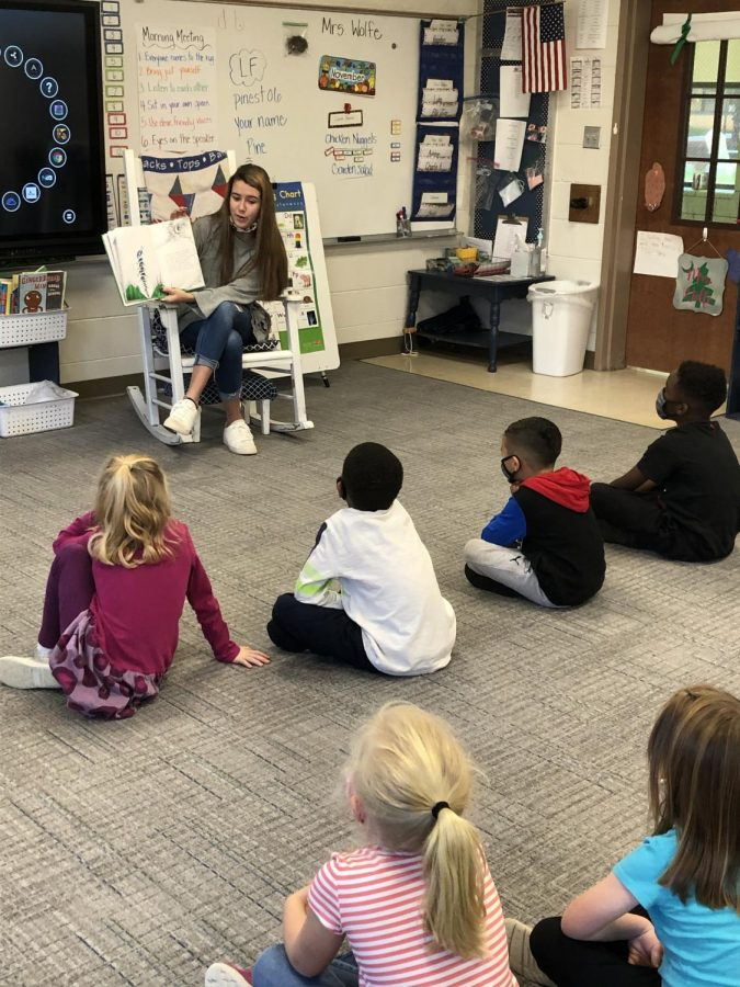 Enthusiastically sharing a story with her class, Teacher Cadet Elise Bryant (12) helps to install the importance of reading to first graders at Pine Street Elementary.