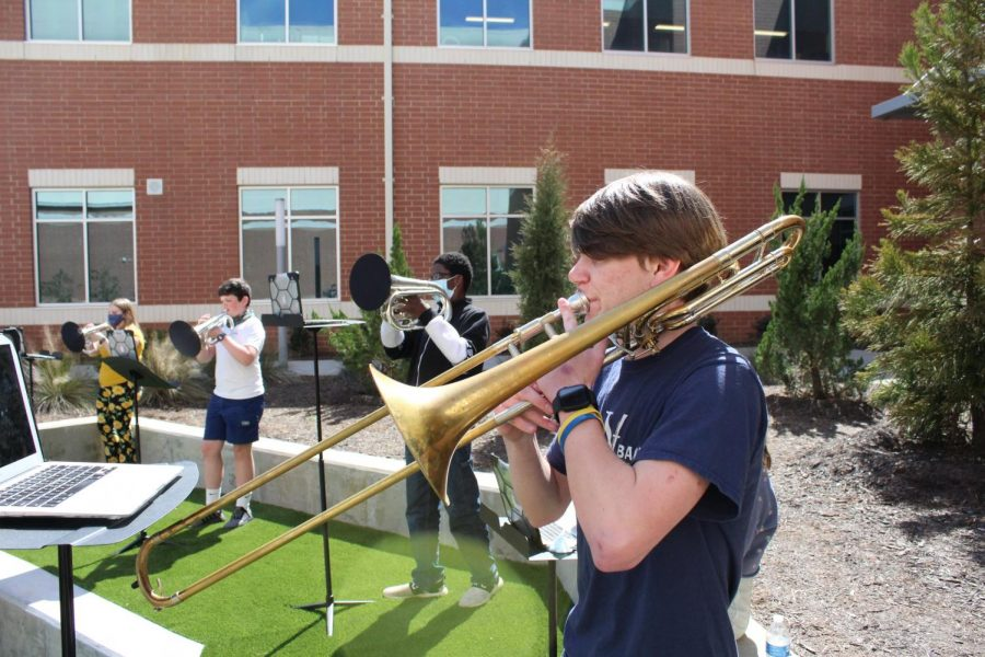Playing the trombone, Thomas Van Vleet (10) joins the band as they play 70s music during the three lunches.