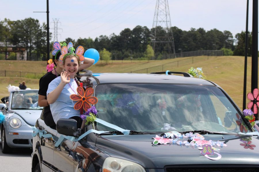 Seniors smile as they pass by Spartanburg High School students cheering.