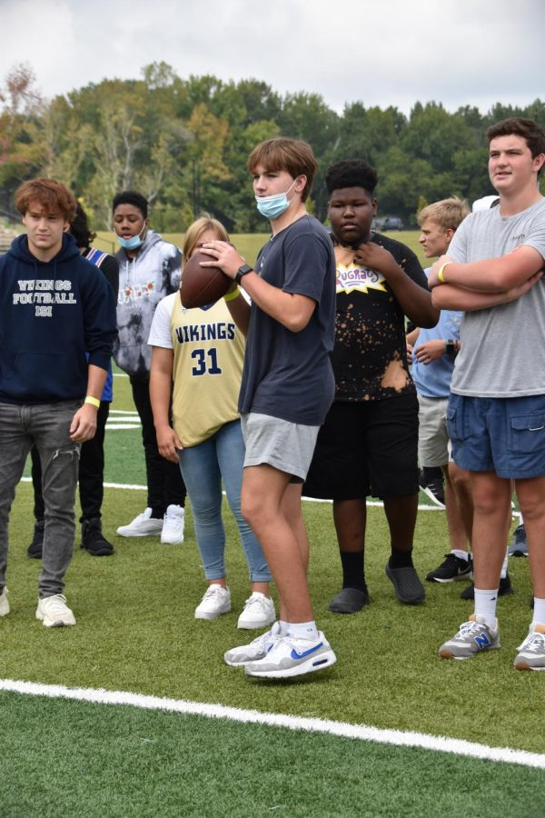 Students take turns throwing the football on the field during Fun Lunch.