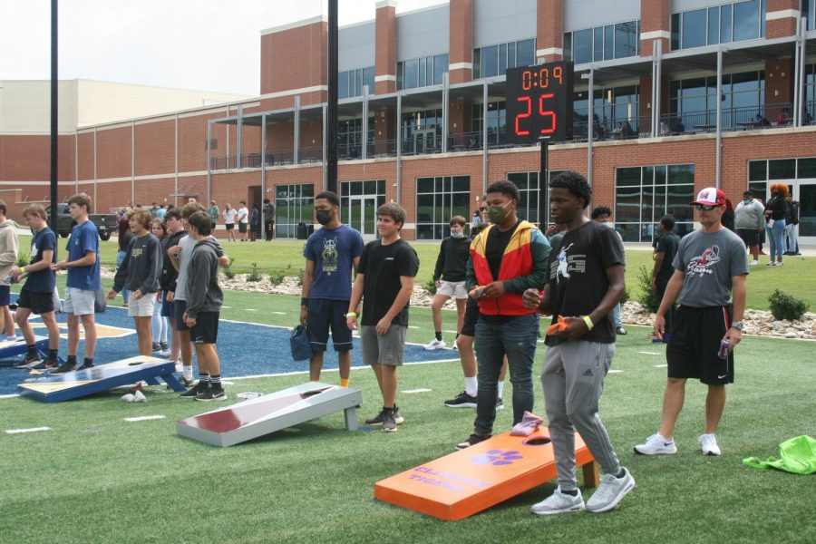 Focused students play cornhole during the Fun Lunch.
